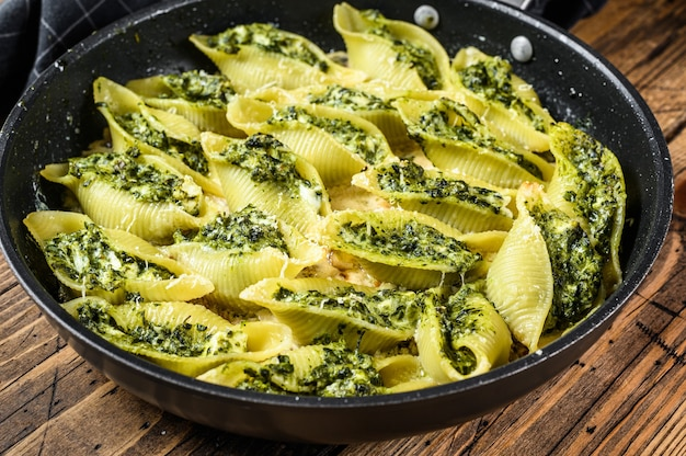 Jumbo shells pasta conchiglioni stuffed with spinach and cheese baked with sauce in a pan on wooden table. top view.