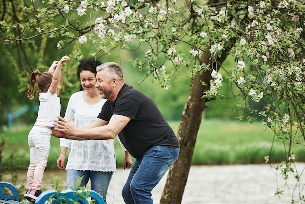 나에게 뛰어. 손녀와 함께 좋은 주말을 야외에서 즐기는 명랑 커플. 좋은 봄 날씨