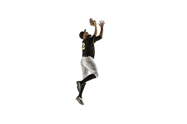 In jump. baseball player, pitcher in black uniform practicing and training isolated on white wall. young professional sportsman in action and motion. healthy lifestyle, sport, movement concept.