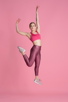 In jump. beautiful young female athlete practicing in studio, monochrome pink portrait