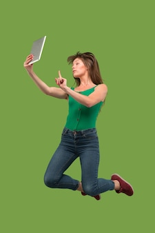 Прыжок молодой женщины над зеленой предпосылкой студии используя гаджет компьтер-книжки или планшета во время прыжка. бегущая девушка в движении или движении.