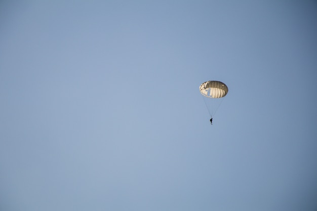 Jump of paratrooper with white parachute, military parachute jumper in the sky.