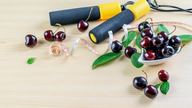 健康管理と適切な栄養のシンボルとして、縄跳び、投薬テープ、新鮮な熟したチェリーベリーをテーブルの上に置きます。