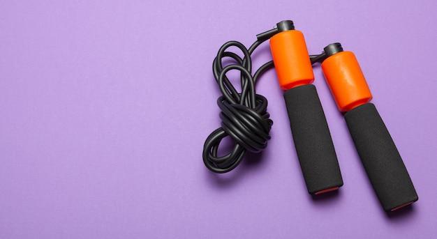 줄넘기. 신체 건강을 위한 재미있는 운동. 검은색 코드가 있는 주황색 로프. 보라색 배경입니다.
