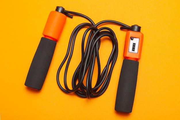 縄跳び。体の健康のための楽しい運動。オレンジ色のロープとジャンプカウンター、黒いコード付き。イエローオレンジ。