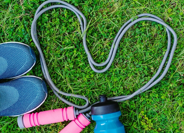 Jump rope, running shoes, and drink bottle on grass background