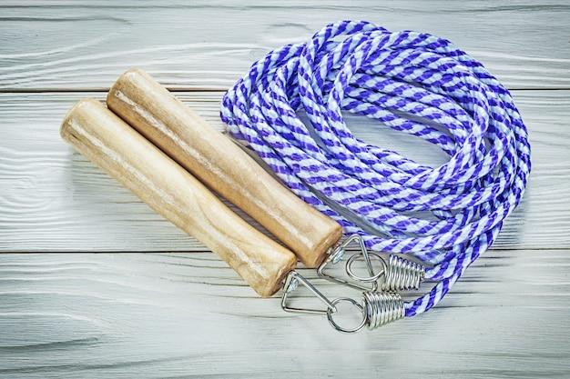 木板のスポーツトレーニングのコンセプトに木製のハンドルが付いている縄跳び