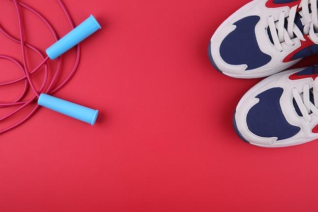 コピースペースのある赤い背景に縄跳びとスニーカー
