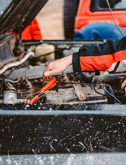 Пусковой запуск разряженного аккумулятора с помощью электрических проводов перемычек.