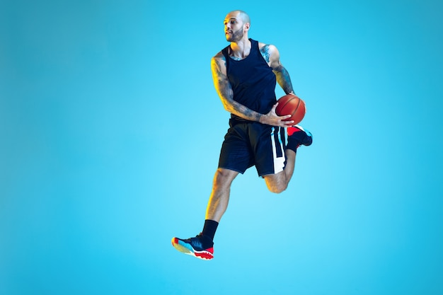 In jump. young basketball player of team wearing sportwear training, practicing in action, motion on blue background in neon light. concept of sport, movement, energy and dynamic, healthy lifestyle.