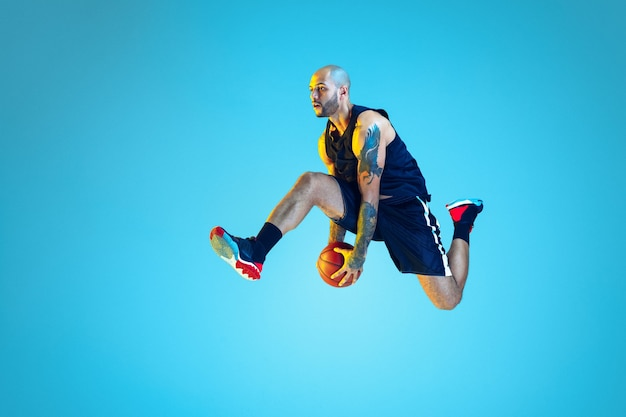 In jump. young basketball player of team wearing sportwear training, practicing in action, motion on blue wall in neon light. concept of sport, movement, energy and dynamic, healthy lifestyle.