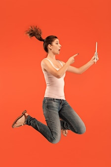Salto di giovane donna su sfondo blu studio utilizzando laptop o tablet gadget durante il salto. ragazza che corre in movimento o in movimento. le emozioni umane e il concetto di espressioni facciali. gadget nella vita moderna