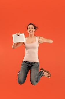 Salto di giovane donna su sfondo blu studio utilizzando tablet gadget durante il salto. . gadget nella vita moderna