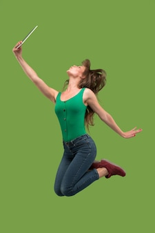 Jump of young woman over green studio background using laptop or tablet gadget while jumping