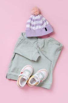 スニーカーとジャンパーと帽子。ピンクの背景に春、秋、夏のベビー服とアクセサリーのセット。ファッションキッズ衣装。フラットレイ、上面図