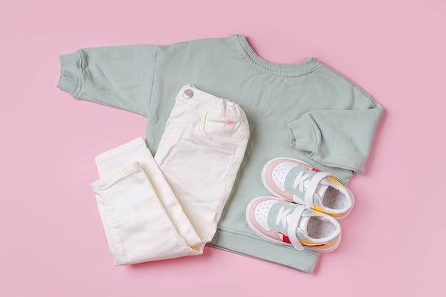 スニーカーとジャンパーとパンツ。ピンクの背景に春、秋、夏のベビー服とアクセサリーのセット。ファッションキッズ衣装。フラットレイ、上面図
