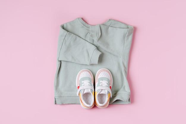 スニーカーとジャンパー。ピンクの背景に春、秋、夏のベビー服とアクセサリーのセット。ファッションキッズ衣装。フラットレイ、上面図