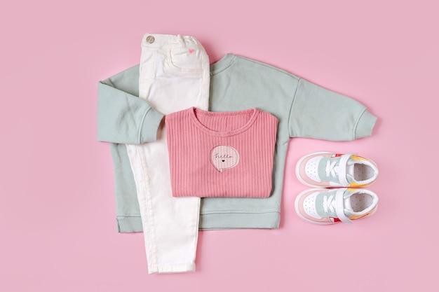 スニーカー付きのジャンパーとパンツ。ピンクの背景に春、秋、夏のベビー服とアクセサリーのセット。ファッションキッズ衣装。フラットレイ、上面図