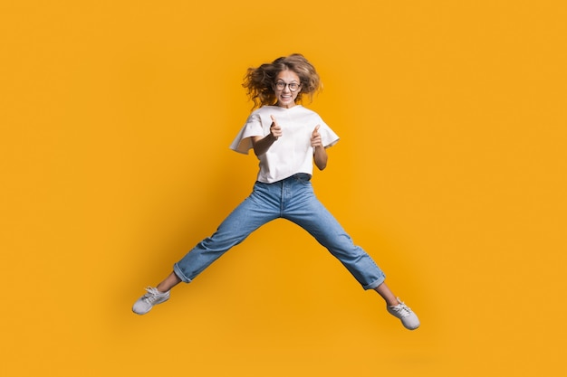 Jumping blonde woman is gesturing the shot and gun with both hands while jumping on a yellow wall at studio