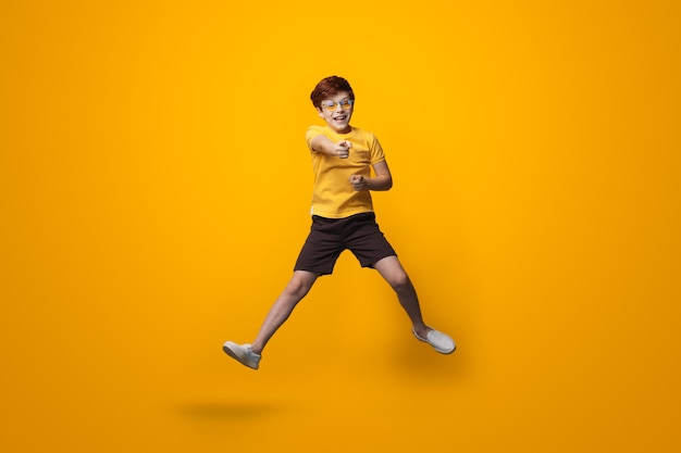 Jumping boy with red hair is wearing glasses and point at camera wearing a yellow shirt on a studio wall