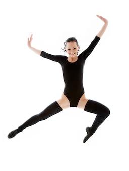 Jumping girl in black leotard over white