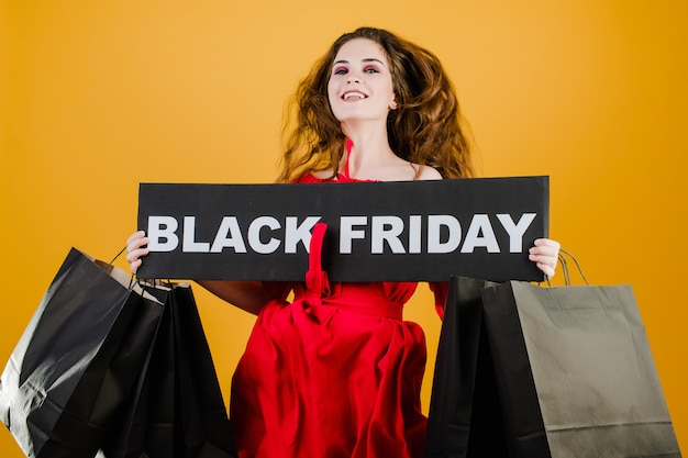 Jumping girl has black friday sign with paper shopping bags isolated over yellow