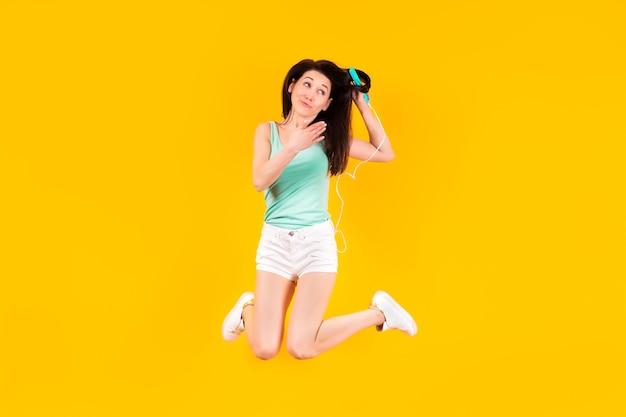 黄色の壁にヘアアイロンの画像で髪をスタイリングするジャンプの女の子