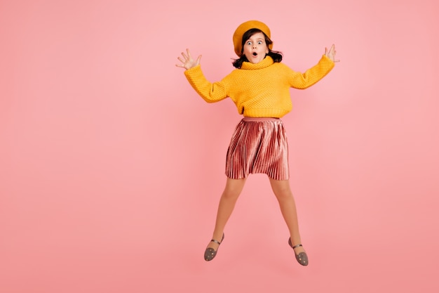 Jumping girl in yellow sweater. excited child dancing on pink wall.