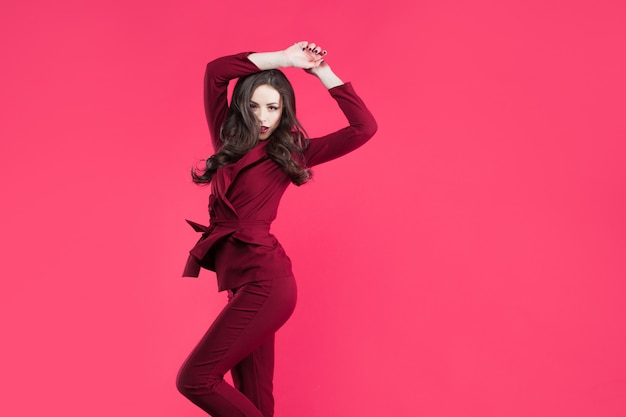 Jumping glamorous girl. attractive young brunette dressed in burgundy color