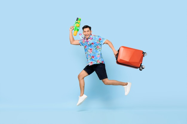 Jumping handsome asian tourist man traveling with water gun and baggage during songkran festival