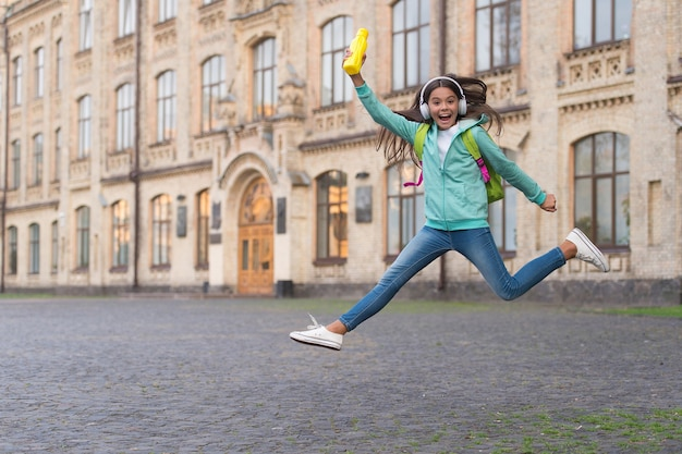 Jumping happy child feel freedom and joy with water bottle outdoor, childhood happiness.