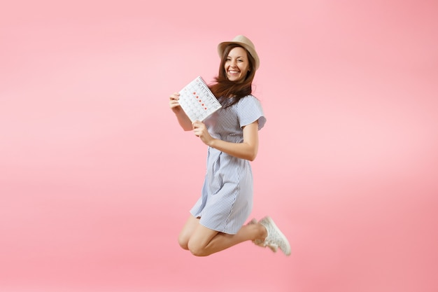 青いドレス、明るいトレンドのピンクの背景に分離された月経日をチェックするための帽子保持期間カレンダーで幸せな楽しい女性をジャンプします。医療、ヘルスケア、婦人科の概念。スペースをコピーします。