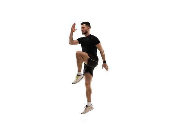 高くジャンプします。白いスタジオでの白人プロスポーツマンのトレーニング。