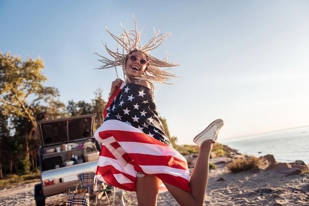 Высокие прыжки. веселая привлекательная женщина, держащая американский флаг, прыгает высоко, чувствуя себя очень счастливой