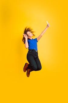 Saltando in alto, prendendo selfie. ritratto della ragazza dell'adolescente caucasico sulla parete gialla. bello modello riccio femminile. concetto di emozioni umane, espressione facciale, vendite, annuncio, educazione. copyspace.