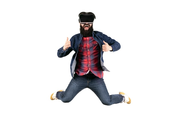 Jumping hipster in glasses of virtual reality showing thumb up, isolated on white wall