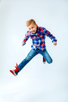 Jumping little boy in the colorful plaid shirt, blue jeans, gumshoes. isolated.
