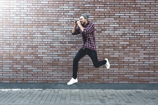 レンガの壁の表面に立っている間、レトロな写真カメラファッション旅行ライフスタイル屋外でジャンプ男