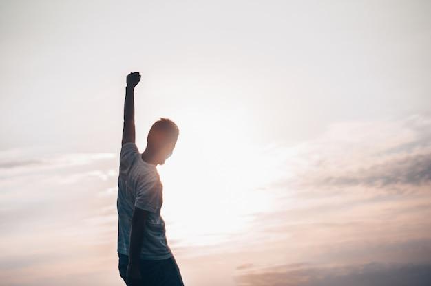 Прыгающий человек. молодой сумасшедший человек прыгает на скалистую вершину над ландшафтом. силуэт прыгающего человека и закатное небо. элемент дизайна. винтажный эффект.