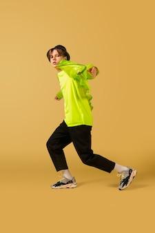 점프. 구식 구식 젊은 남자 춤에 고립 된 노란색 스튜디오