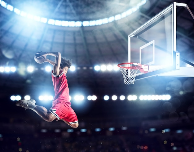 Jumping player throws the ball in the basket in the stadium full of spectators