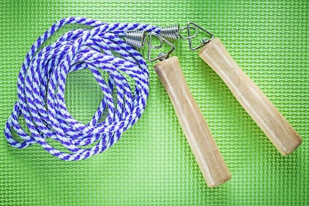 緑の背景のスポーツトレーニングのコンセプトに縄跳び