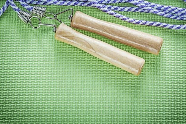 緑の表面スポーツトレーニングコンセプトの木製ハンドル付き縄跳び