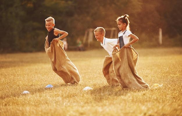 야외 필드에서 자루 경주를 점프. 아이들은 화창한 낮에 신나게 놀고 있습니다.