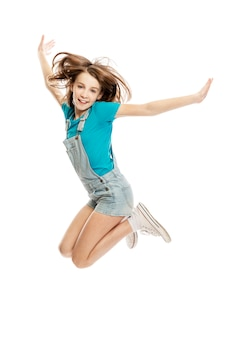 Jumping teenage girl in denim overalls and blue tank top. freedom and happiness. . vertical.