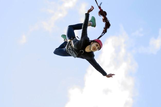밧줄로 점프 용감한 소녀는 다리에서 뛰어 내려 하늘을 날다