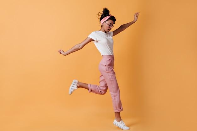 Donna che salta in pantaloni rosa