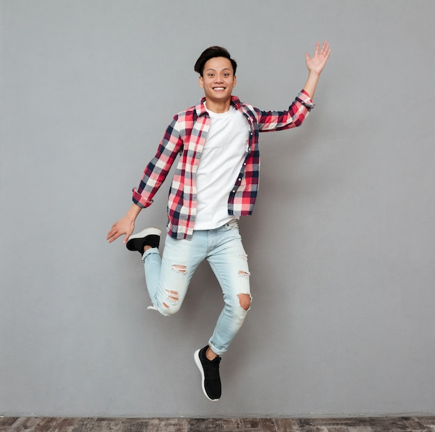 Jumping young asian man.