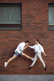 Прыжки молодая пара перед зданиями на бегу в прыжке в высоту
