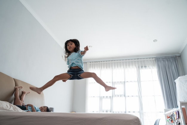 Jumping young kid on the bed